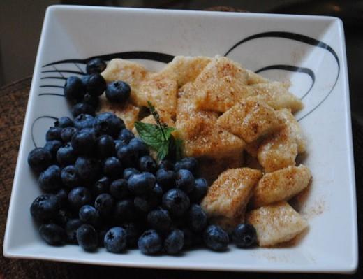 Leniwe pierogi podane ze stopionym masłem, cukrem trzcinowym, cynamonem i borówkami