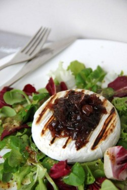 Grilled Camembert served on the bed of salad with vinaigrette sauce and onion preserves / Grillowany Camembert na łożu z sałaty z sosem vinaigrette i konfiturami z cebuli